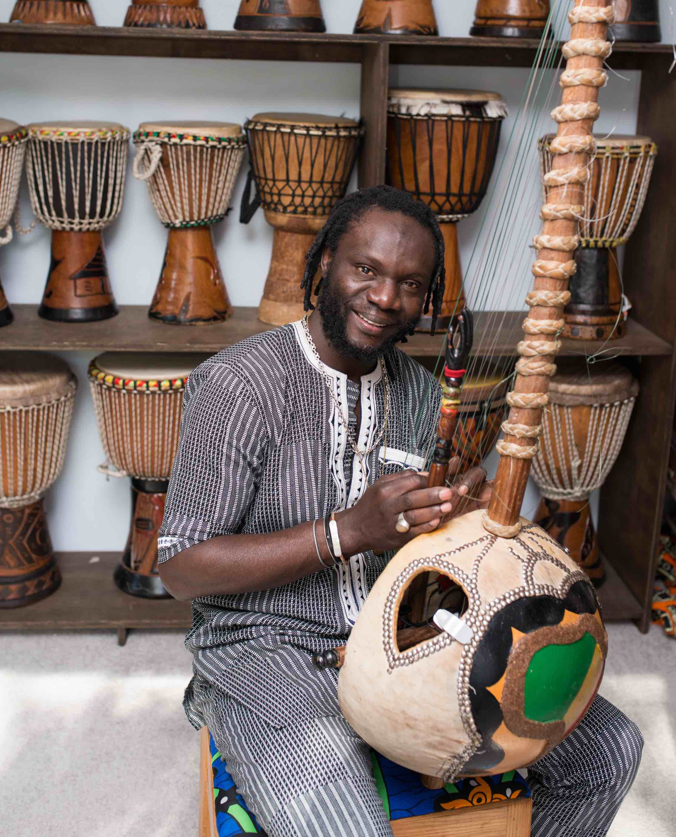 Diali Cisshiko with his collection of traditional drums and the kora.